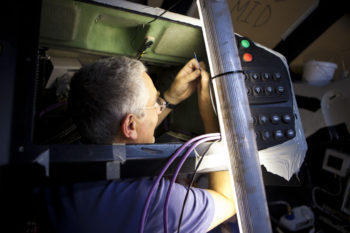 electrician wiring up the helm of a vessel